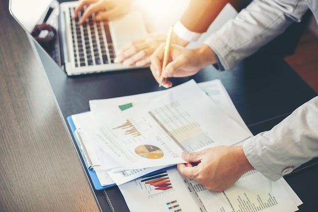 Donne di affari asiatiche che tengono una penna e documenti di analisi e diagramma finanziario del grafico