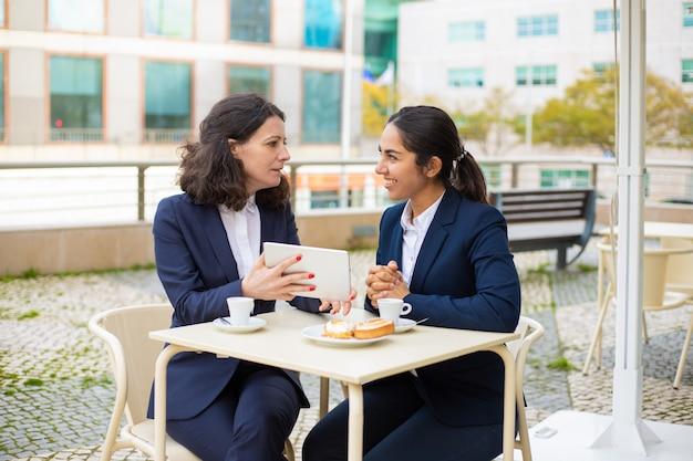 Donne di affari che bevono caffè e che per mezzo del pc della compressa