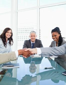 Donne di affari che sorridono nel corso di una riunione mentre esaminano i colleghi che agitano le mani