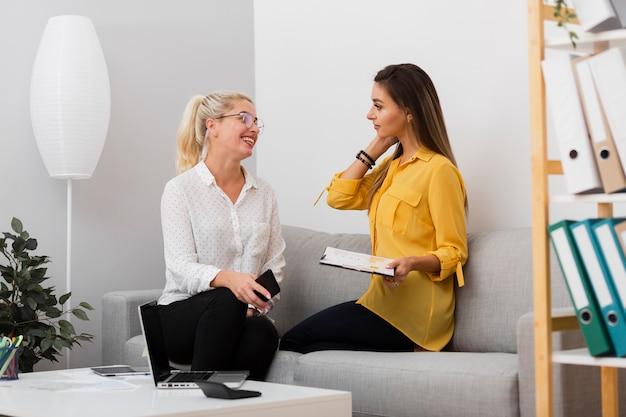 Donne di affari che tengono un telefono e una lavagna per appunti