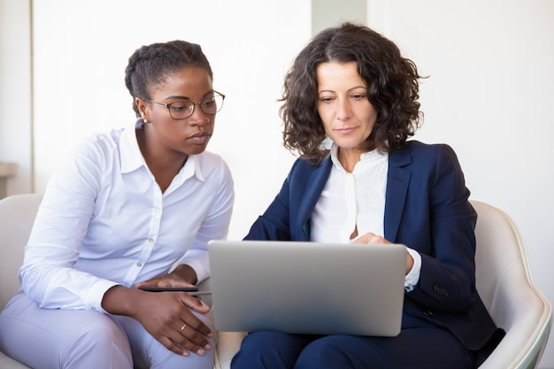 Donne di affari serie che guardano insieme presentazione