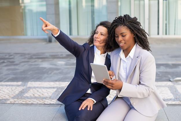 Donne di affari sorridenti che per mezzo del pc della compressa
