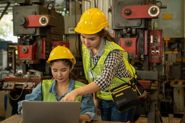 Donne di ingegneria che utilizzano un computer portatile che funziona nella fabbrica, concetto di tecnologia della fabbrica.