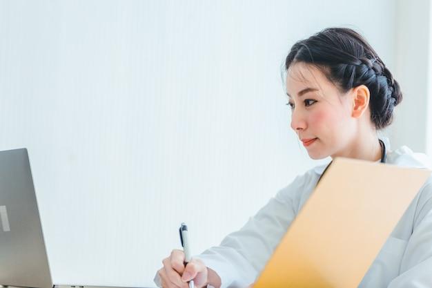 Donne di medico del ritratto che si siedono lavorare alla lavagna per appunti della nota in ufficio medico