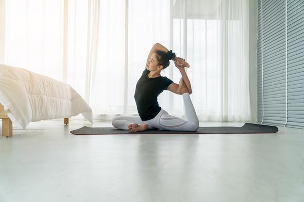 Donne di mezza età che fanno yoga in camera da letto al mattino, esercizio fisico e relax al mattino.
