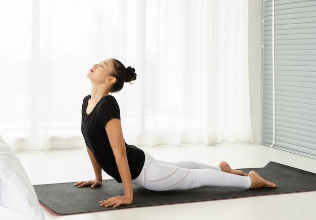 Donne di mezza età che praticano yoga posa rivolta verso l'alto del cane o urdhva mukha svanasana posa. meditazione con yoga in camera da letto bianca dopo il risveglio al mattino. concetto di esercizio fisico e assistenza sanitaria.