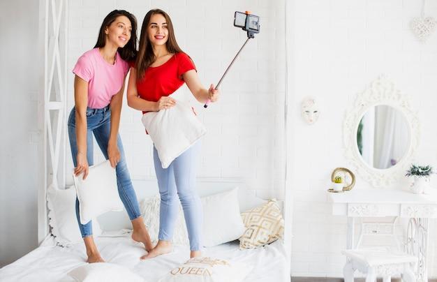 Donne di smiley a letto con il cuscino che cattura foto