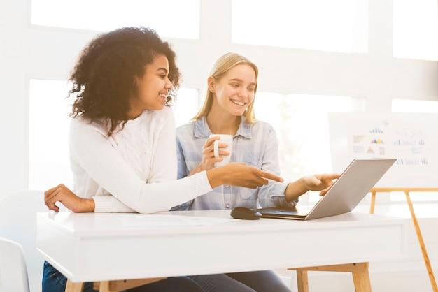 Donne di smiley che lavorano al computer portatile