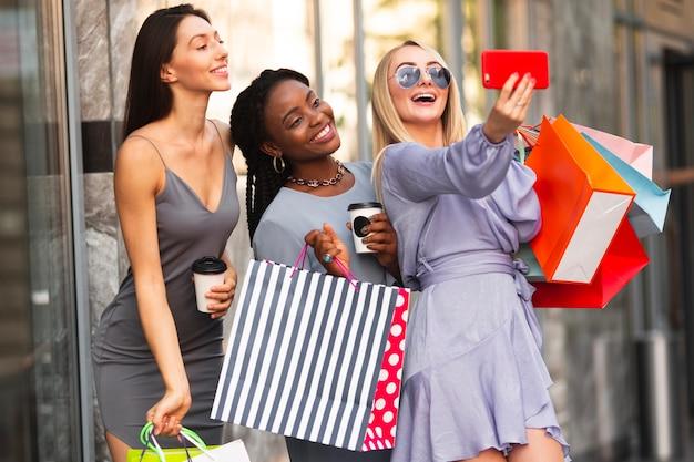 Donne di smiley che prendono selfie all'aperto