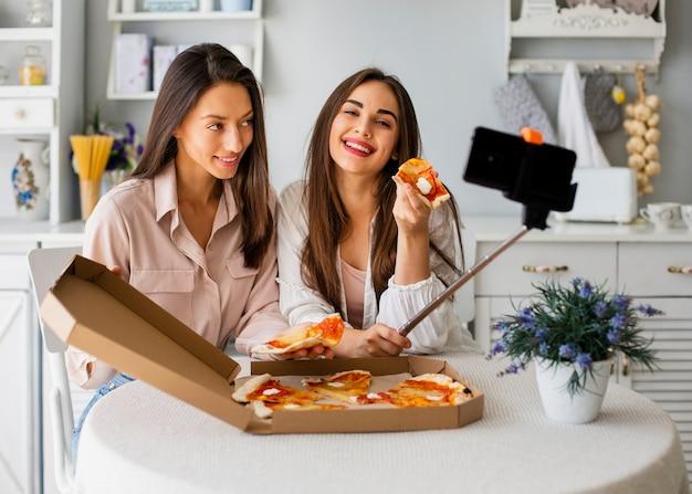 Donne di smiley che prendono selfie mentre mangiando