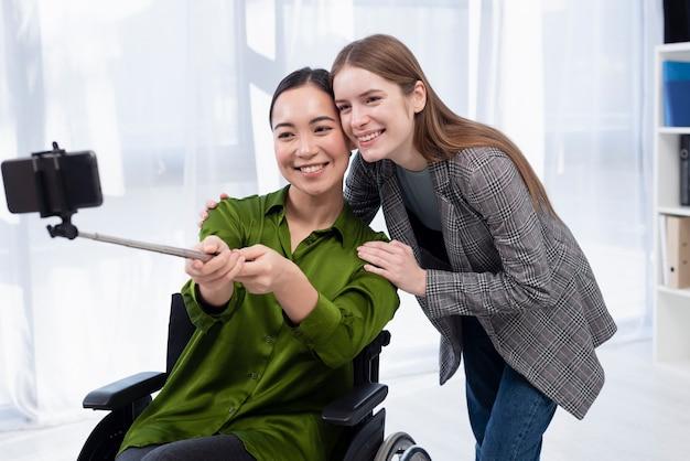 Donne di smiley che prendono selfie