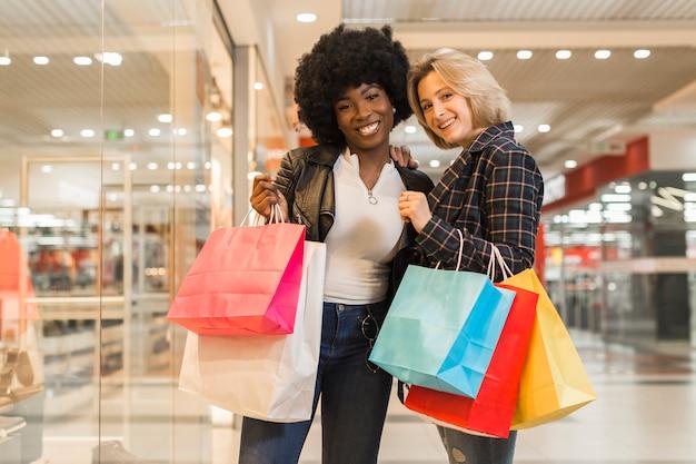 Donne di smiley di vista frontale che comperano al centro commerciale