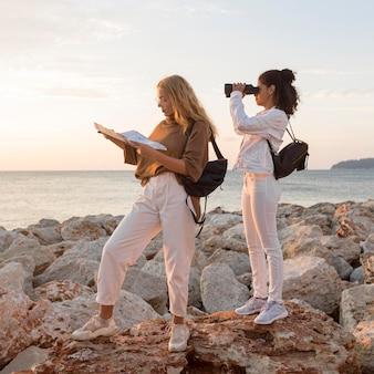 Donne di vista laterale con mappa e binocolo