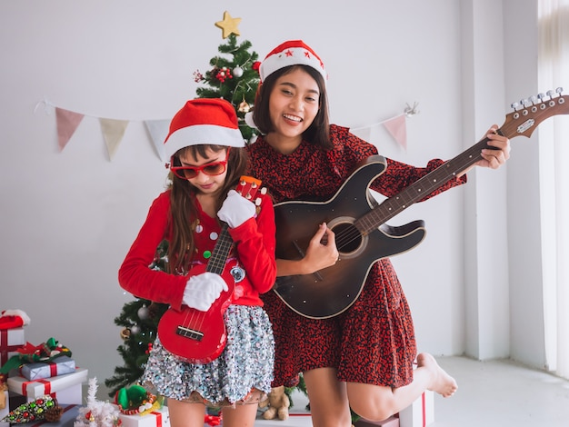 Donne e bambini asiatici festeggiano il natale strimpellando la chitarra in casa, una ragazza suona una canzone con un sorriso il giorno di natale