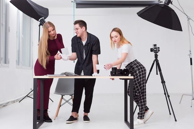 Donne e uomo che guardano attraverso le foto in studio