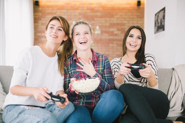 Donne eccitate che bighellonano con videogame e snack