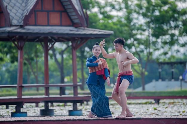 Donne ed uomo della tailandia nel ballo tailandese del costume nazionale