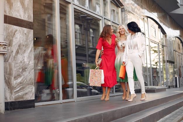 Donne eleganti con borse della spesa in una città
