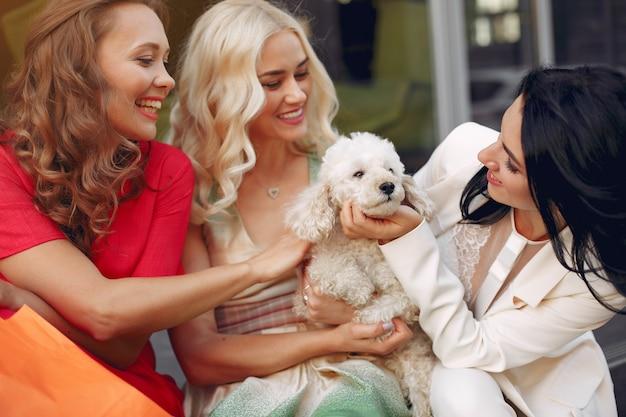 Donne eleganti con cagnolino in una città