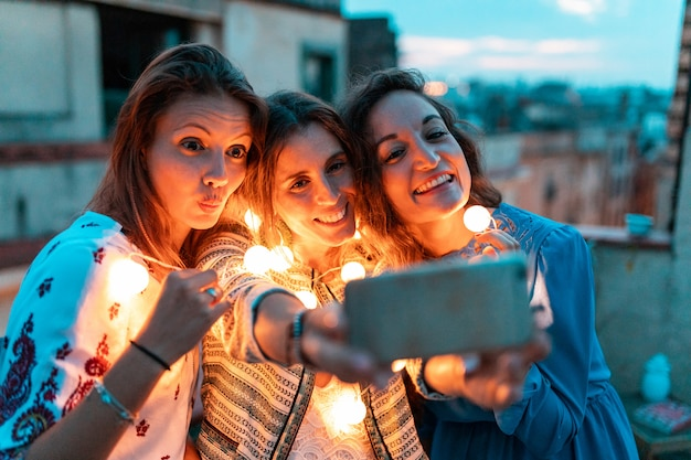 Donne felici che prendono insieme un selfie alla festa sul tetto di notte
