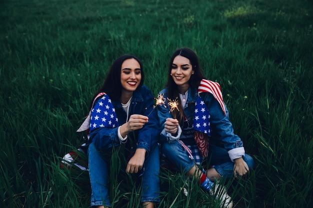 Donne felici che si siedono sull'erba con le luci di bengala