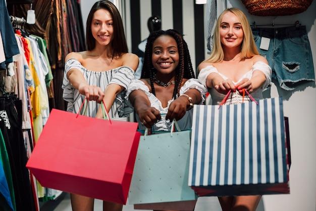 Donne felici che tengono i sacchetti della spesa