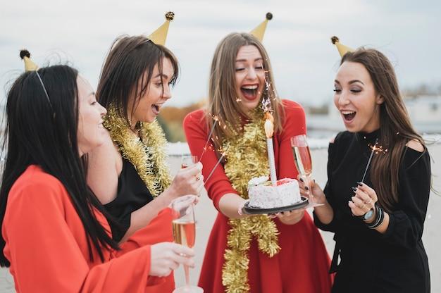 Donne felici che tengono una torta di compleanno
