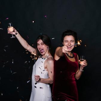 Donne felici con bicchieri di champagne e stelle filanti