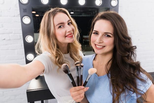 Donne felici con le spazzole che prendono selfie nello studio di bellezza