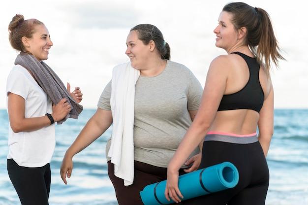 Donne felici del colpo medio alla spiaggia