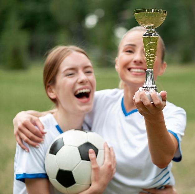 Donne felici del colpo medio che tengono premio