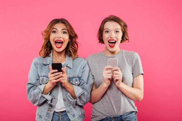 Donne felici eccitate che chiacchierano dai telefoni.