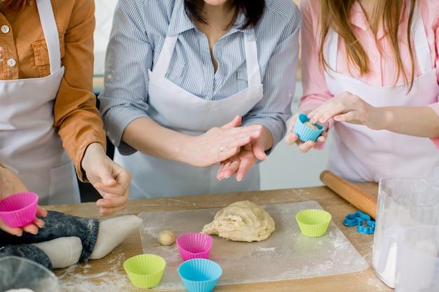 Donne felici in grembiuli bianchi che cuociono insieme. foto del primo piano delle mani delle donne e di piccolo bambino che preparano pasta per i muffin bollenti. concetto di famiglia, cucina, cottura e persone