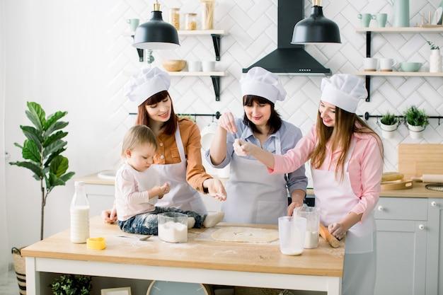 Donne felici in grembiuli bianchi che cuociono insieme, ritagliando le forme dalla pasta del biscotto di zucchero con le formine per biscotti. la piccola neonata aiuta a fare i biscotti insieme a madre, zia e nonna