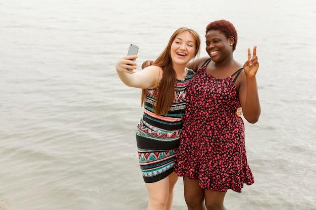 Donne felici in spiaggia prendendo selfie