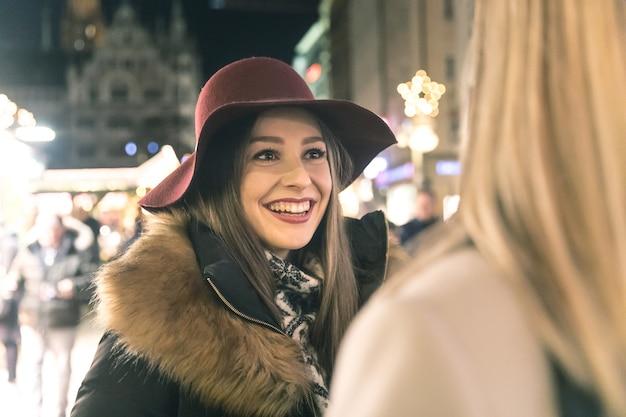Donne felici incontro e chiacchierando al mercatino di natale a monaco di baviera