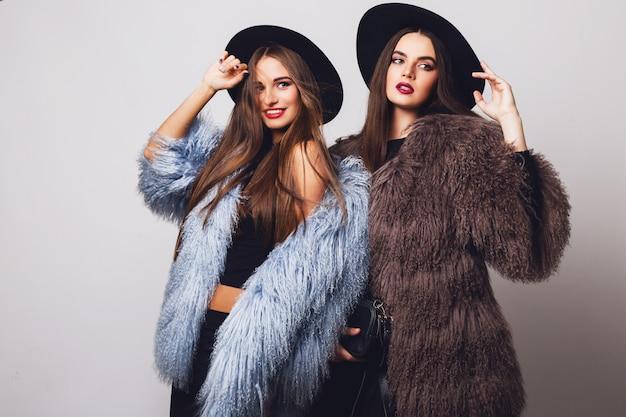 Donne graziose affascinanti che posano e indossano pellicce