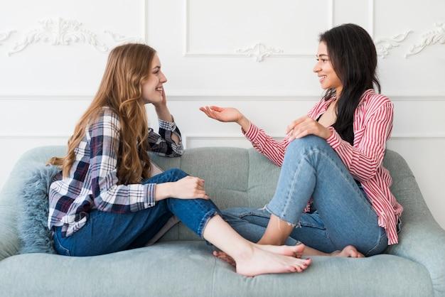 Donne graziose che chiacchierano mentre sedendosi sul sofà