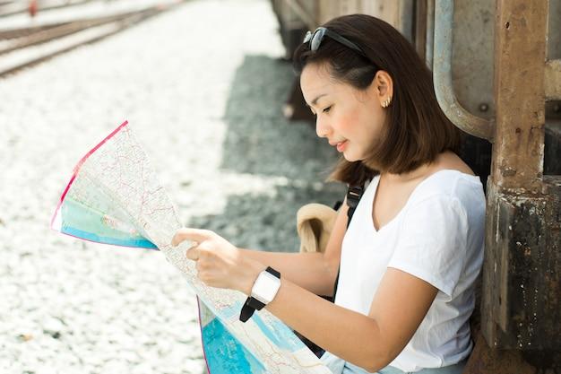 Donne graziose che guardano una mappa per il viaggio in treno la tailandia