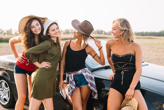 Donne graziose vicino al cabriolet nero