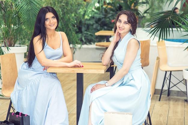 Donne in abiti eleganti seduti a un tavolo