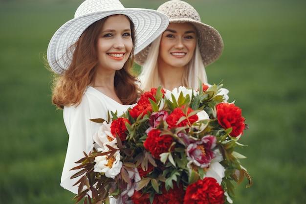 Donne in abito elegante in piedi in un campo estivo