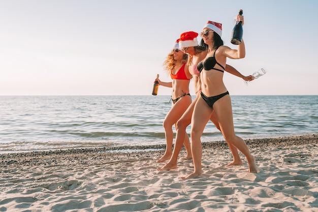 Donne in bikini con cappello santa e champagne