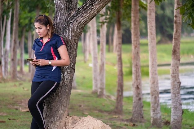 Donne in buona salute che si rilassano nel giardino e giocano smartphone
