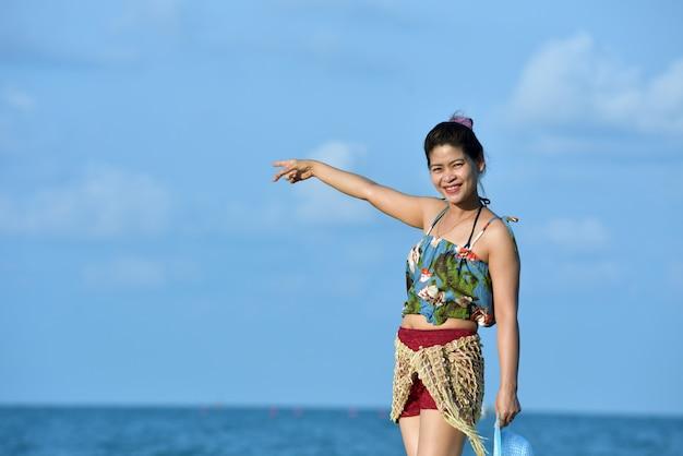Donne in costume da bagno alla moda che riposa sulla spiaggia di sabbia