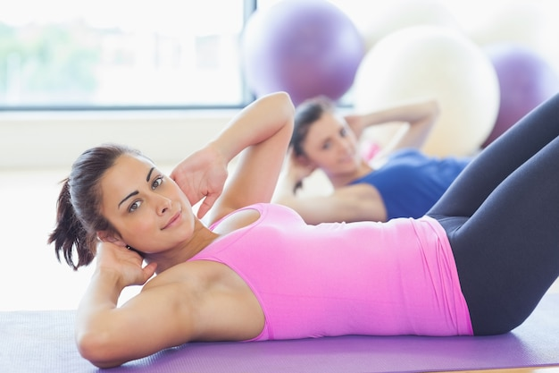 Donne in forma facendo esercizi di pilates in palestra