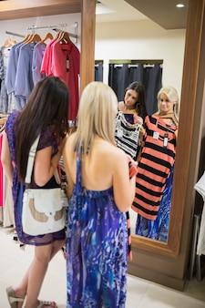 Donne in piedi allo specchio alzando i vestiti