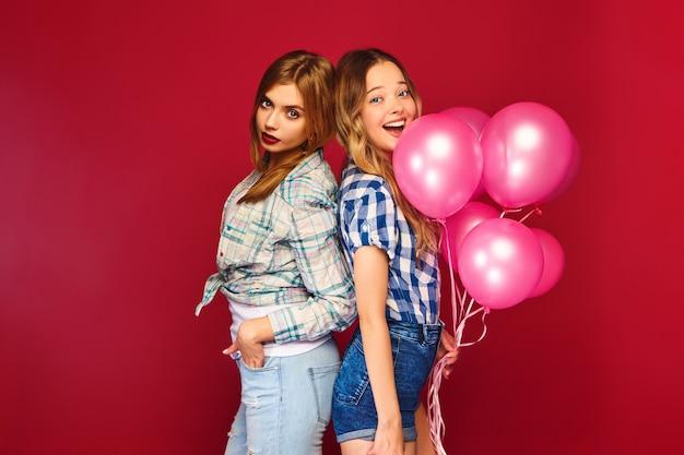 Donne in posa con confezione regalo grande e palloncini rosa