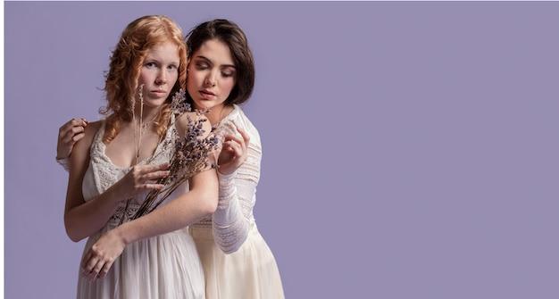 Donne in posa con un bouquet di lavanda mentre abbracciano e copiano lo spazio