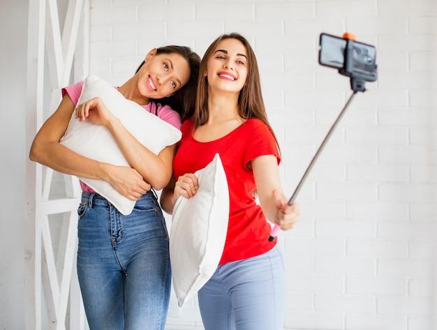 Donne in possesso di cuscino e prendendo selfie